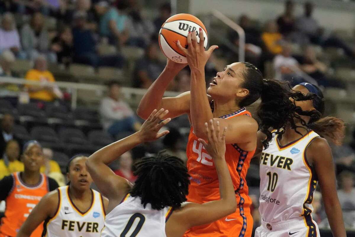 Connecticut Sun's Brionna Jones (42) shoots against Indiana Fever's Kelsey Mitchell (0) during the first half of a WNBA basketball game Thursday, July 1, 2021, in Indianapolis. (AP Photo/Darron Cummings)