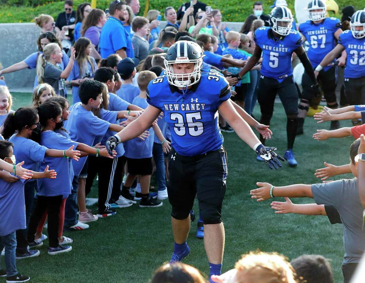 New Caney tight end Jaiden Hataway (35) gives kids high-fives as he walks toward the field before a high school football game at Randall Reed Stadium, Friday, Sept. 3, 2021, in New Caney.