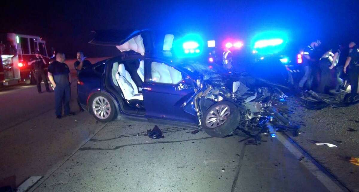 Authorities investigate a crash involving law enforcement and a Tesla on Feb. 27, 2021 in Montgomery, Texas.