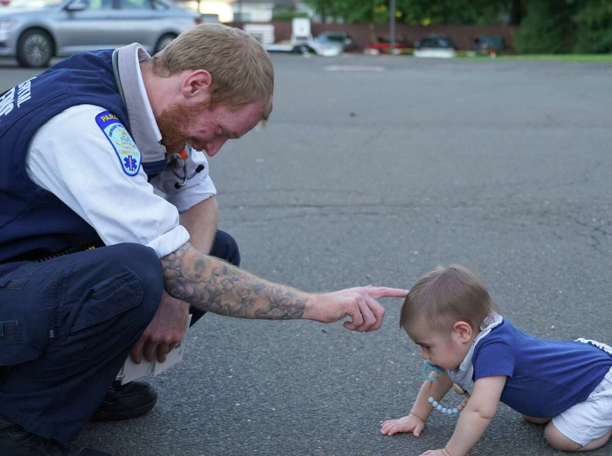 Dan Bach met 14-month old Ryan Martin for the second time on Friday, when his parents, Angela and Peter Martin came to thank Bach for saving their child's life, on Sept. 24 behind the EMS building on South Avenue in New Canaan