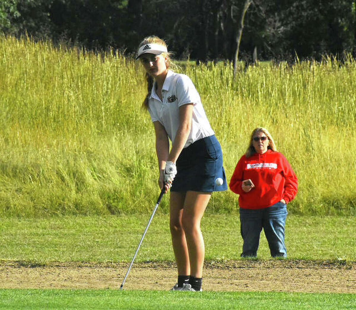 Father McGivney's Ellie Hyten chips a shot onto the green on No. 16 at Oak Brook Golf Club during a dual against Alton.