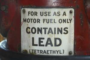 A sign on a vintage gasoline pump advises that the gas contains lead (tetraethyl). (Photo by Robert Alexander/Getty Images)