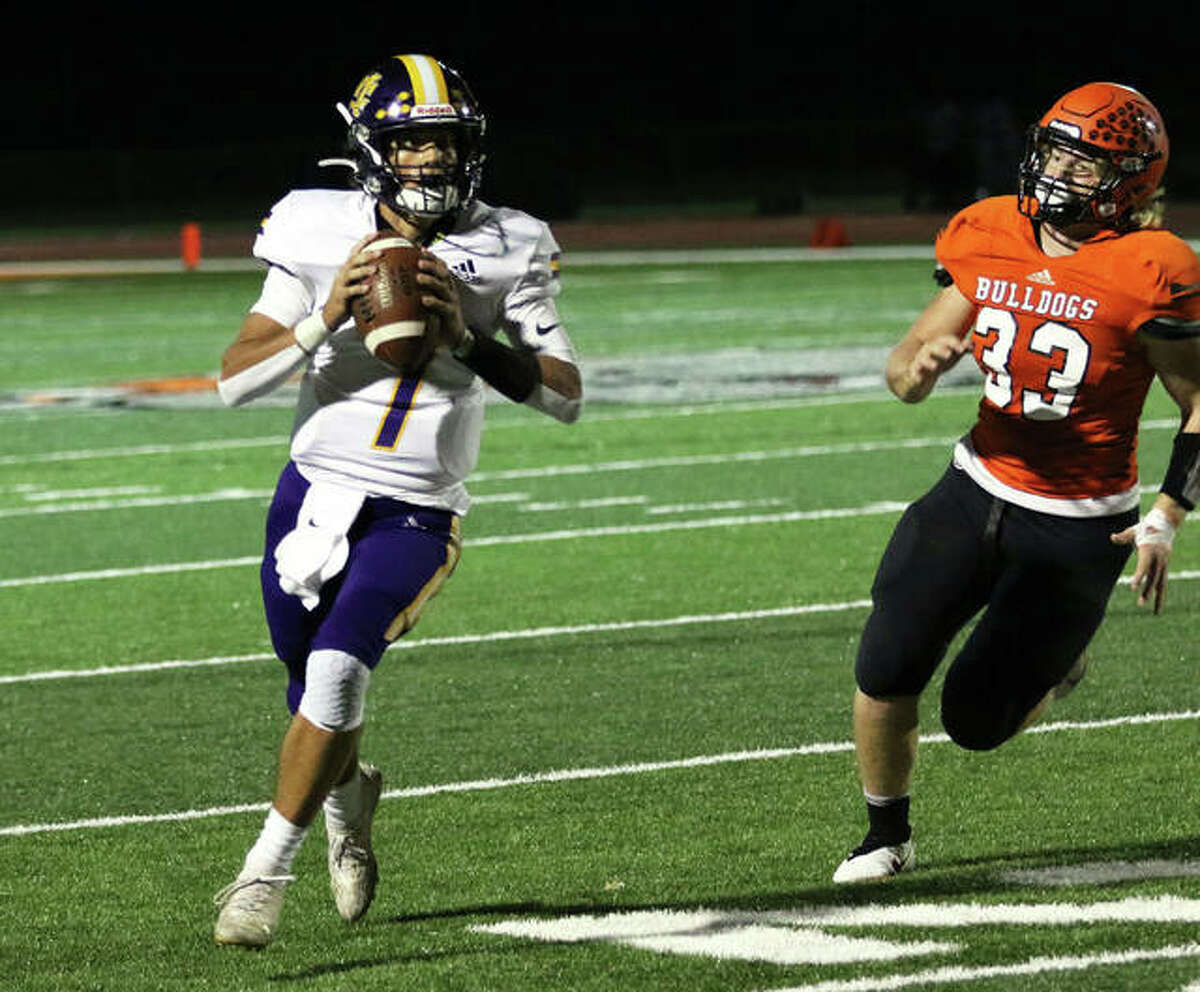CM quarterback Bryer Arview rolls out and looks for a receiver with Waterloo linebacker Max Mitchell (33) applying pressure before Arview found Logan Turbyfill for a 9-yard TD pass on fourth down late in the fourth quarter Friday night in Waterloo.