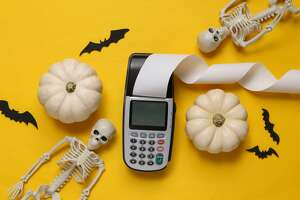 Halloween decor and payment terminal on yellow background. Halloween shopping