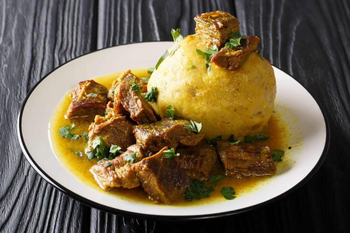 A stock image of spicy mofongo with plantains, garlic and chicharron served with meat and broth.