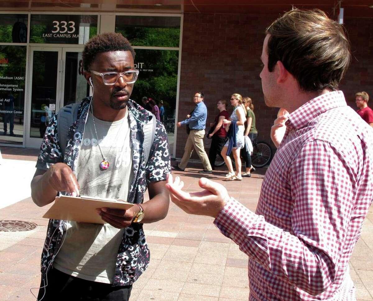University of Wisconsin freshman Kellen Sharp (left) gets voter-registration information NextGen worker Sean Manning.