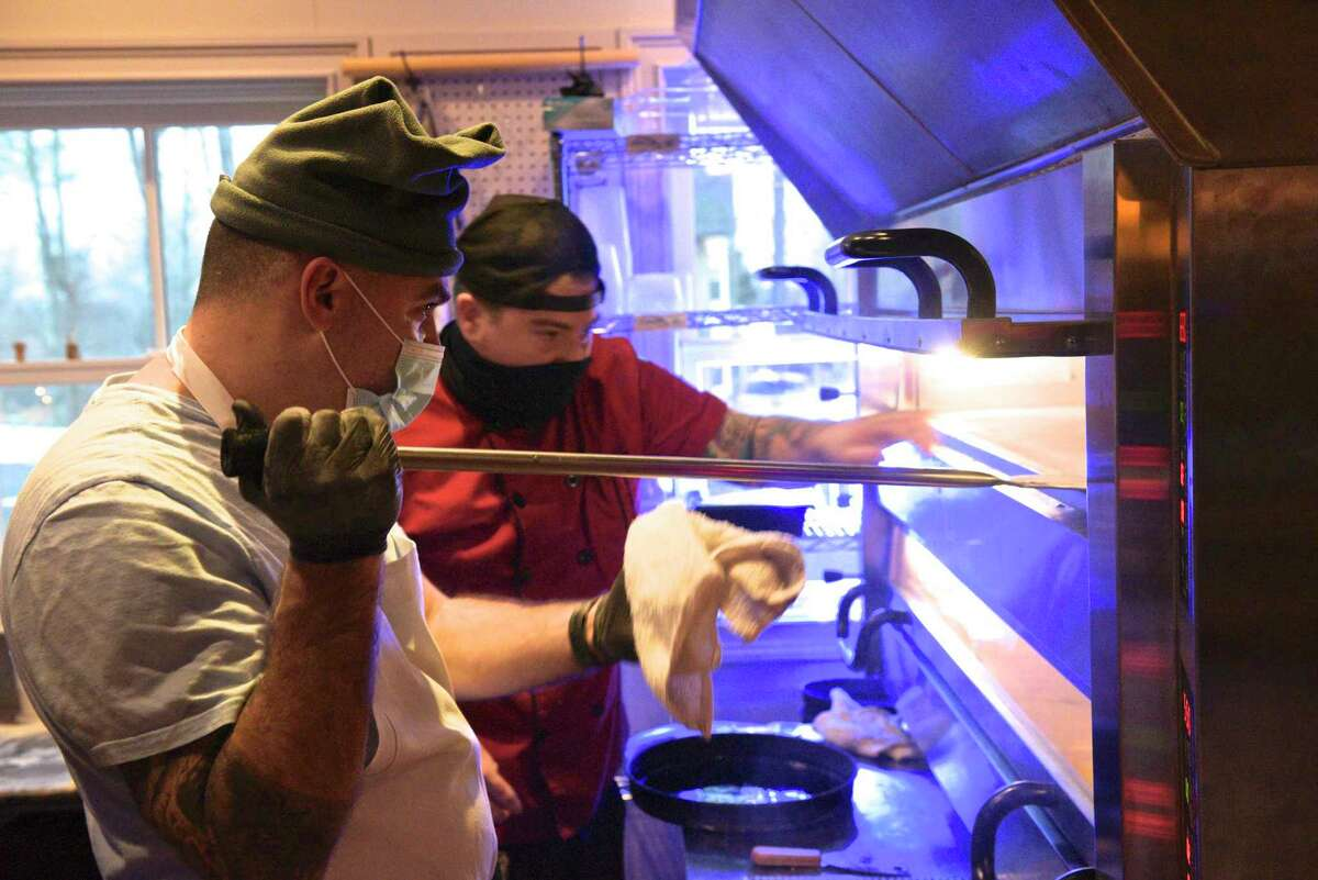 Pizza Guys Matteo Stanz, left, and Dan Rooney check on a pizza in the oven at Good Old Days Pizzeria and Cocktail Den, in the lower level of Marygold's on Main. The restaurant had its opening night on Wednesday, December 30, 2020, in Newtown. Conn.