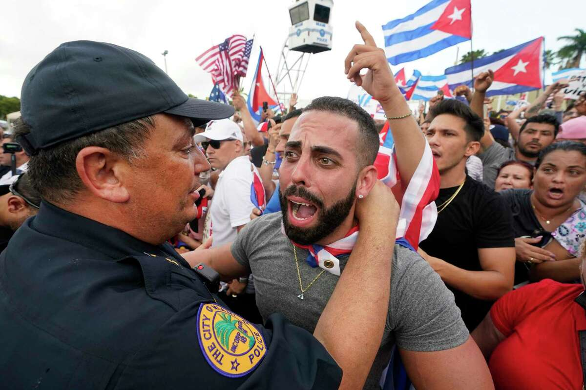 FILE - In this Wednesday, July 14, 2021, file photo, Miami Police Chief Art Acevedo, left, hugs a demonstrator, in Miami's Little Havana neighborhood, as people rallied in support of antigovernment demonstrations in Cuba. City of Miami commissioners held a special meeting in which they attacked Acevedo less than six months into his post, and voted to further investigate him and his appointment. (AP Photo/Wilfredo Lee, File)