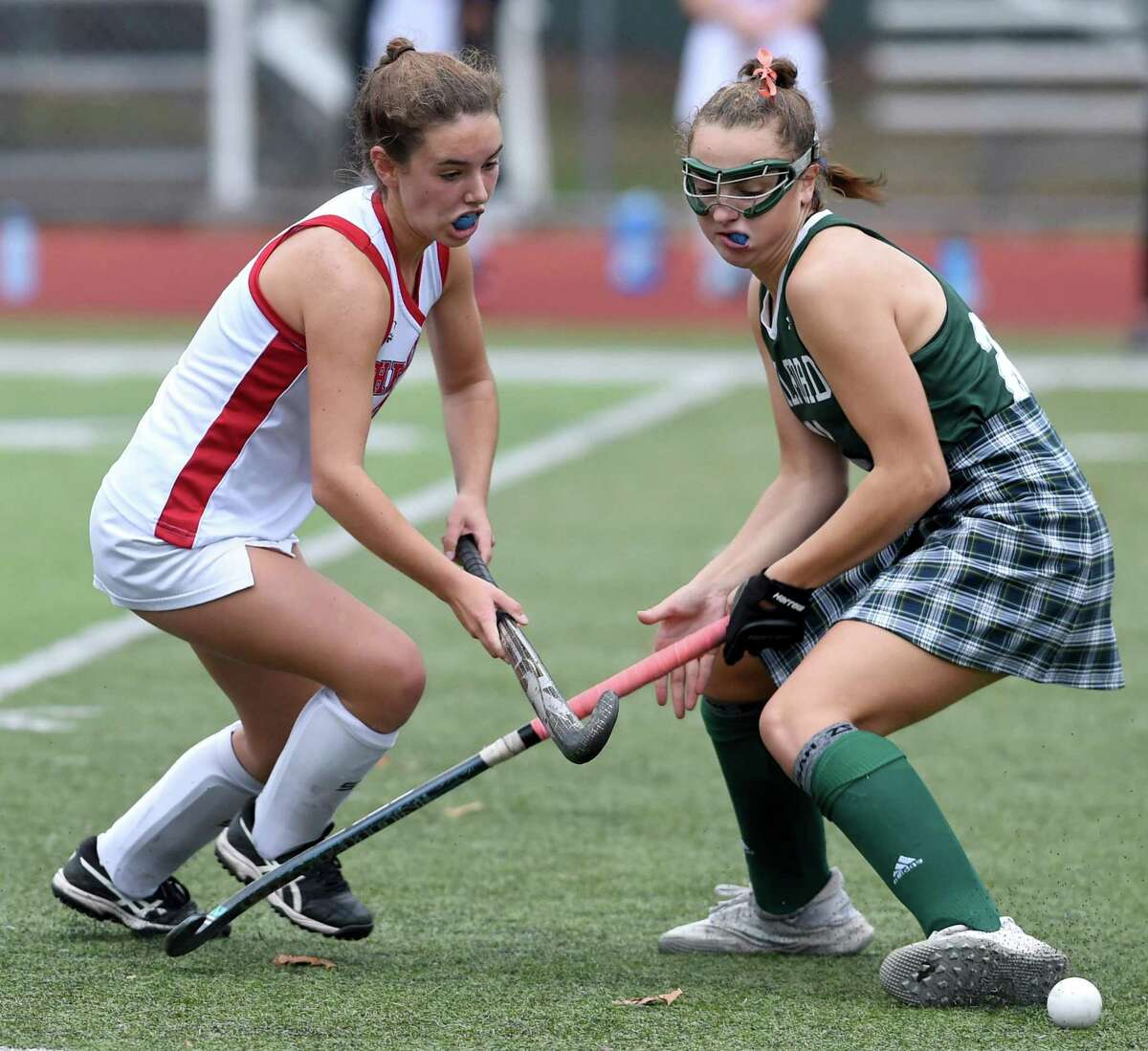Leah Black of Cheshire (left) and Maddie Epke of Guilford fight for the ball in the SCC Division A field hockey championship at Cheshire High School on November 11, 2020.