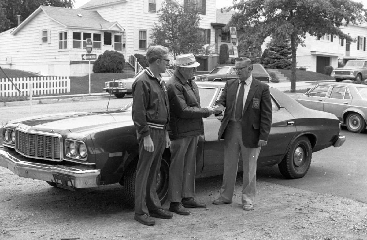 A former Manistee City Police Department car will be put to use by the city's housing commission for the mobile meals program, a food service for older adults which brings hot meals to the homes of eligible residents. (From left) Howard Fenton and Harold Marsh of the housing commission accept the keys from Public Safety Director John Willet, whose department donated the vehicle for the mobile meals program. The photo was published in the News Advocate on Sept. 30, 1981. (Manistee County Historical Museum photo)
