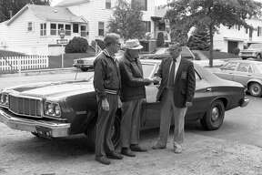 A former Manistee City Police Department car will be put to use by the city's housing commission for the mobile meals program, a food service for the elderly which brings hot meals to the homes of eligible senior citizens. (From left) Howard Fenton and Harold Marsh of the housing commission accept the keys from Public Safety Director John Willet, whose department donated the vehicle for the mobile meals program. The photo was published in the News Advocate on Sept. 30, 1981. (Manistee County Historical Museum photo)