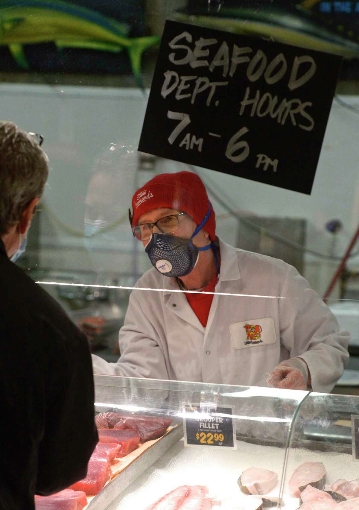 Zig Zavory, of Danbury, of New Milford, wears a mask while working in the seafood department at Stew Leonard's today, less than 24 hours after the implementation of Gov. Ned Lamont's order directing masks to be worn in public setting where social distancing is not possible. Danbury, Conn. Tuesday, April 21, 2020.