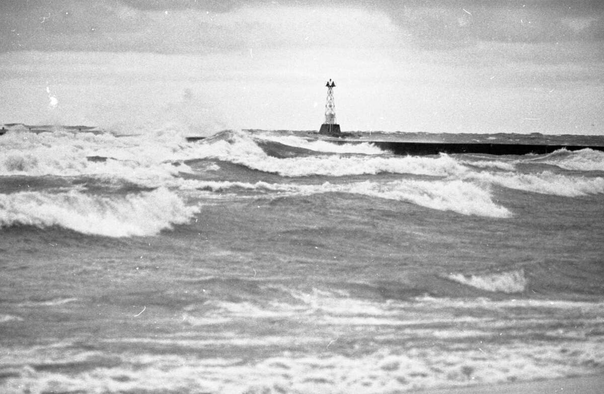 Gale winds pushed high waves over the First Street Beach pier this morning as the winds of autumn began stirring up Lake Michigan. Gale winds of up to 42 knots with waves from 6 to 12 feet have been forecast. The photo was published on Oct. 1, 1981 in the News Advocate. (Manistee County Historical Museum photo)
