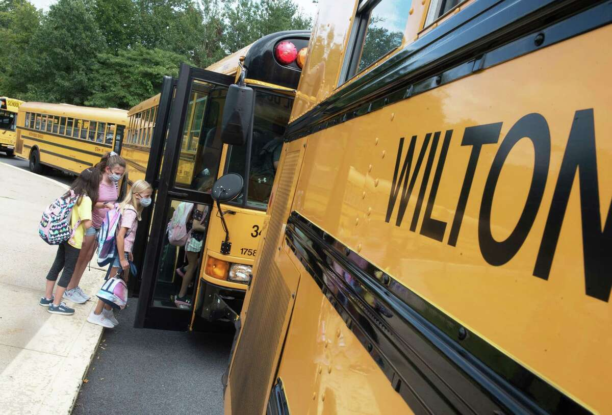 Cider Mill Students head to their buses after the first day of school on Aug. 30, 2021, in Wilton, Conn. A school bus shortage is causing a problem for sports teams throughout the state.