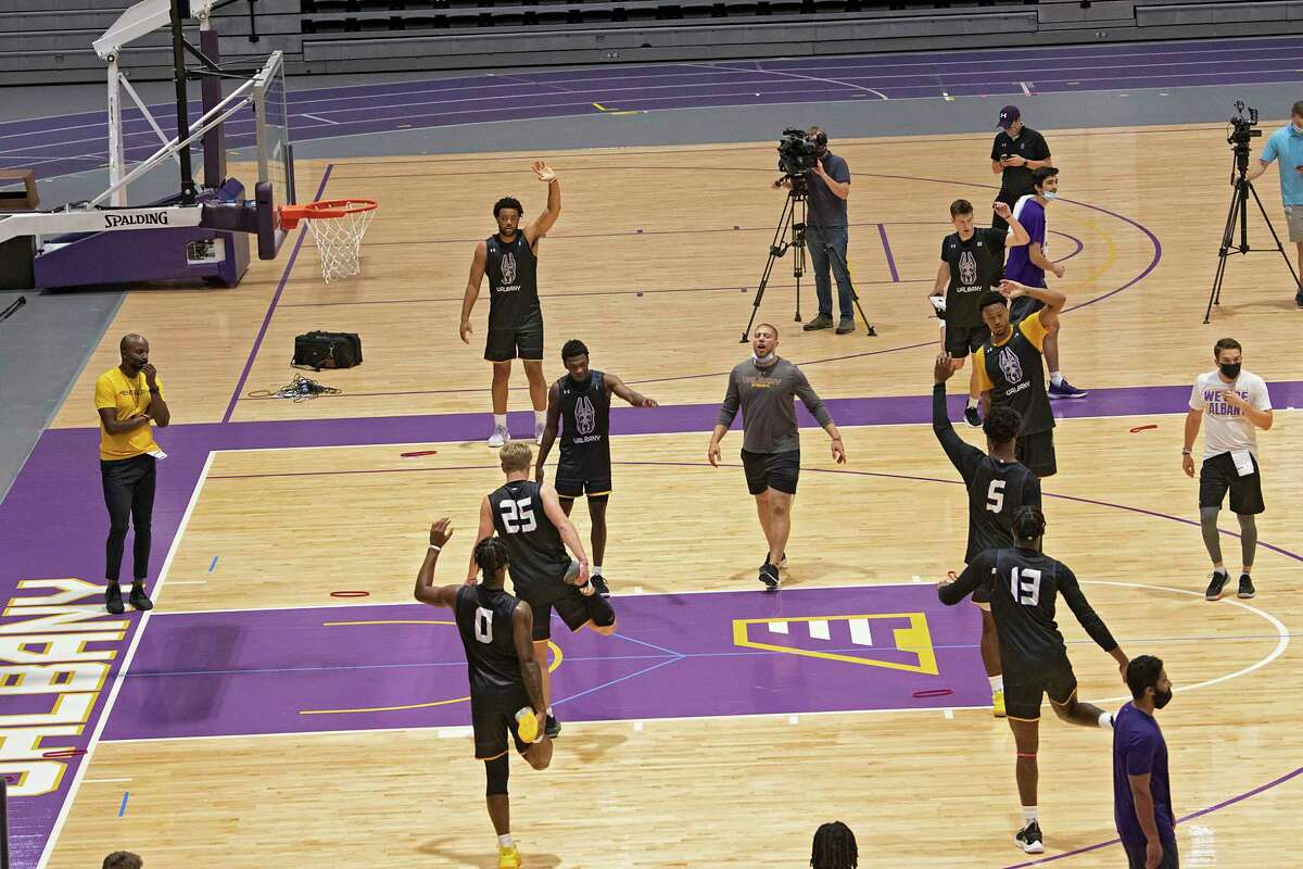 University at Albany men's basketball head coach Dwayne Killings, left, watches his team warm up during his first official practice with the team on Tuesday, Sept. 28, 2021 in Albany, N.Y.