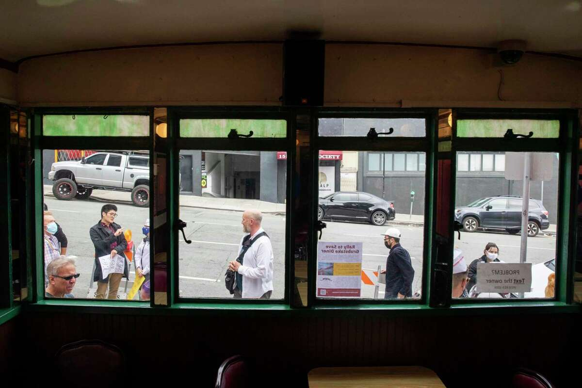 Rally participants are seen through the windows of the Grubstake Diner on Pine Street in San Francisco. Supporters and regulars of the historic Grubstake Diner are protesting against an appeal of a project they're backing to remodel the crumbling diner and building housing on top of it.
