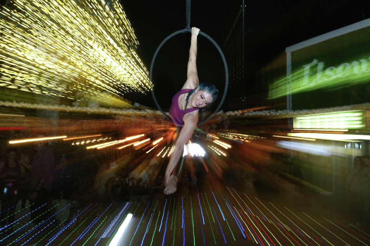Michelle Kaplowitz performs on aerial ropes at Elsewhere Garden Bar & Kitchen. Kaplowitz has been an aerialist for 10 years, even after being diagnosed with a traumatic brain injury that puts her at risk for seizures.