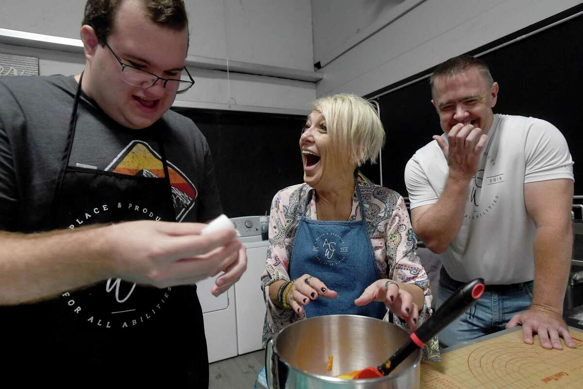 Honey Staudenmier andd Russell Watley laugh as Paul Deslatte accidentally sprays egg on a team member while cracking them during a cooking session at Ability Central Works, a vocational program promoting the skills and development of teens and adults who have been identified with disabilities. Photo made Tuesday, September 21, 2021 Kim Brent/The Enterprise