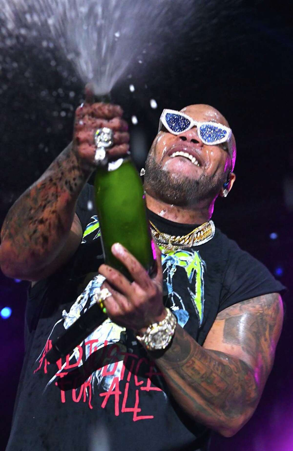 """Rapper Tramar Dillard, better known by his stage name Flo Rida is shown popping a bottle of champagne during his """"live"""" in concert performance at The Big E in West Springfield, Massachusetts on Sept. 25, 2021."""
