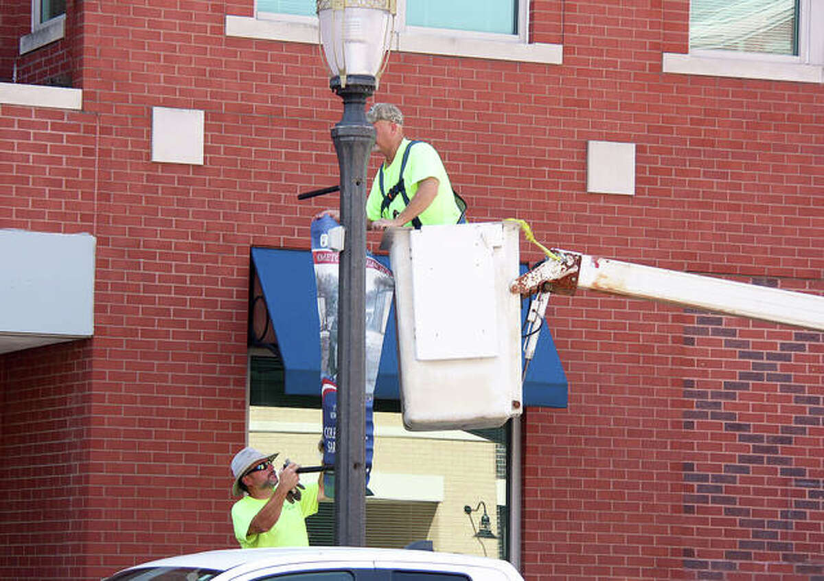 Edwardsville Public Works Department employees, Danny Liliensiek and Paul Brooks, hang Veterans Day banners on light poles on N. Main Street Monday.