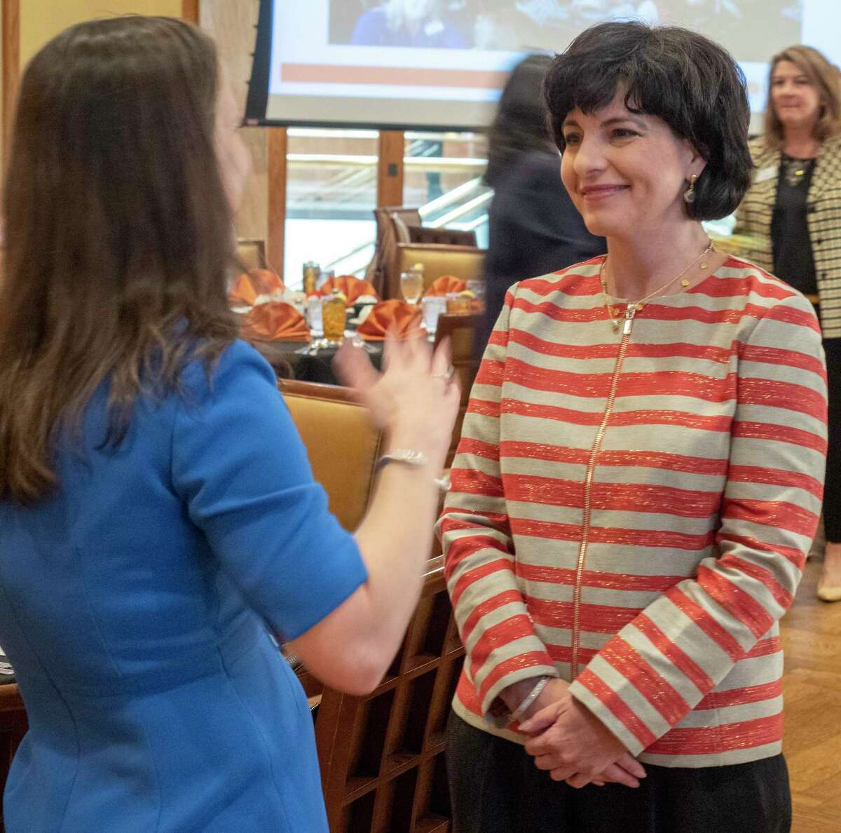 Texas Railroad Commissioner Christi Craddick, talks with Kristin Schmidt before speaking at the Women's Energy Network luncheon.