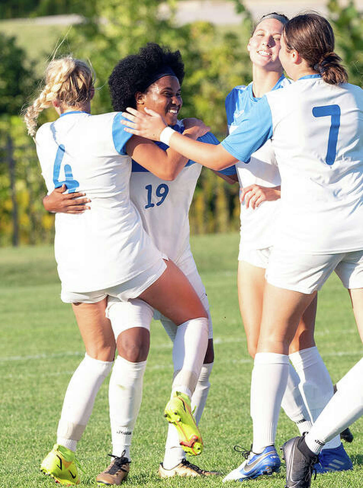 LCCC's Chrissy Mitchell (19) is congratulated by teammates Skylar Hollingshead (4), Lauren Kirkby (7) and Kaya Thies after scoring the game-winning goal against Illinois Central College Tuesday at LCCC.