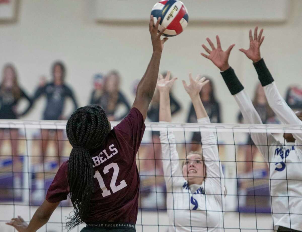 Legacy High's Christallynn Tate tries for a kill as Midland High's Grace Utter and Aniya Clinton try to block 09/28/2021 at the Midland High gym. Tim Fischer/Reporter-Telegram