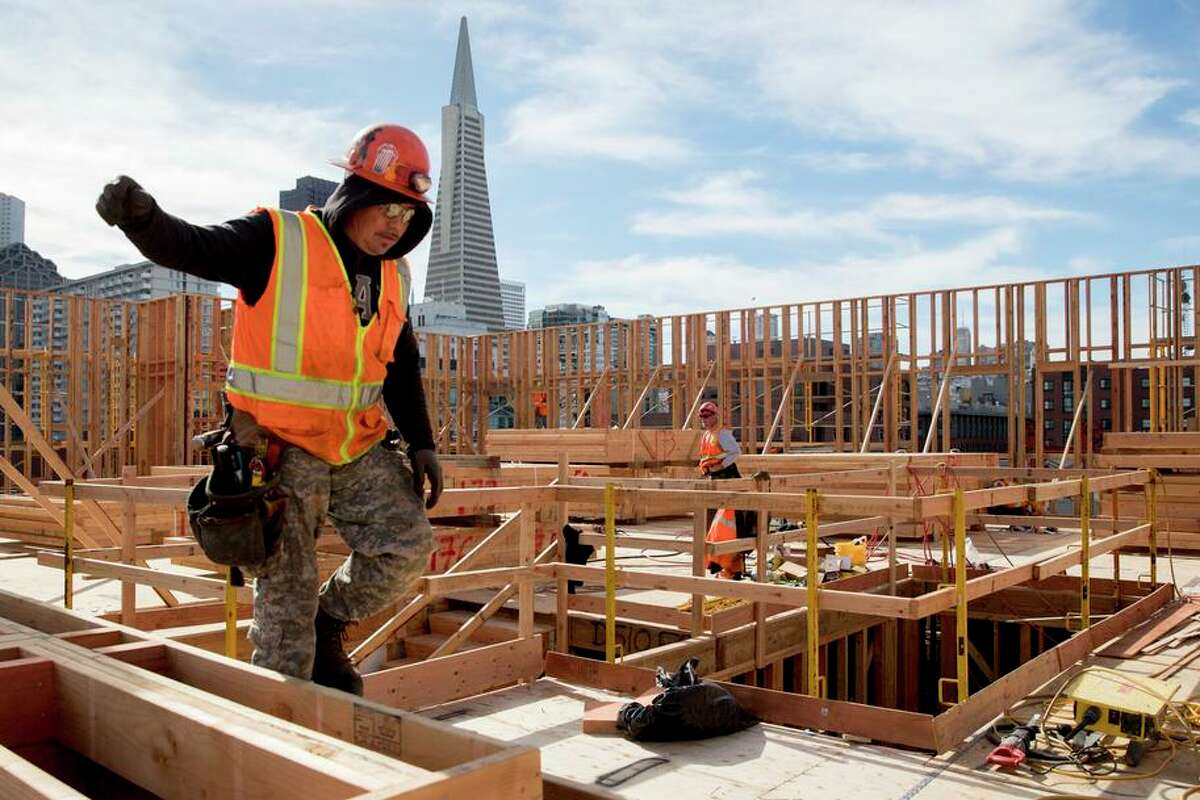 The Trans- america Pyramid peeks out behind wooden walls as workers continue construction on two affordable housing develop- ments, one for seniors and one for multifamily use, along the Embarcadero near Broadway.