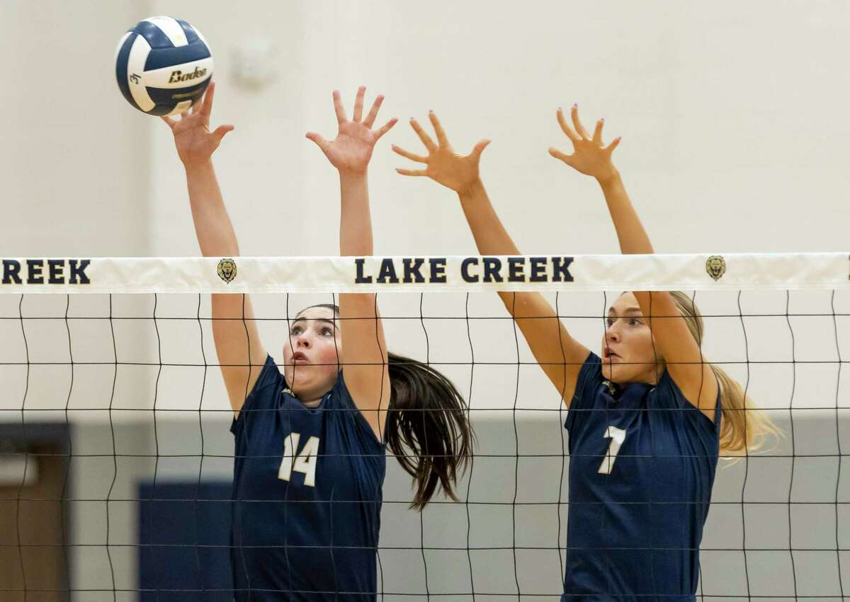 Kinzie Riley of Lake Creek (14) and Lauren Hilty (7) block the ball during the first set of a District 20-5A match against Cleveland at Lake Creek High School, Tuesday, Sept. 28, 2021, in Montgomery.