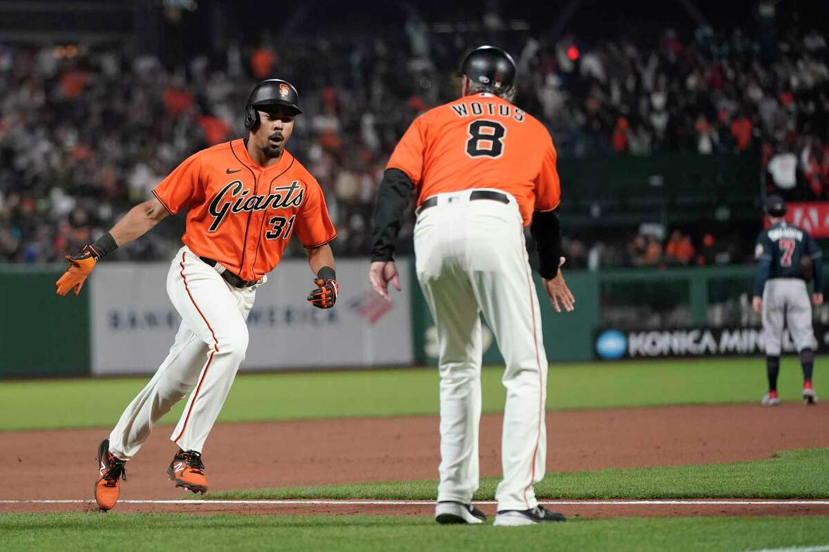 San Francisco Giants' LaMonte Wade Jr., left, celebrates after hitting a home run with third base coach Ron Wotus against the Atlanta Braves during a baseball game in San Francisco, Friday, Sept. 17, 2021. (AP Photo/Jeff Chiu)