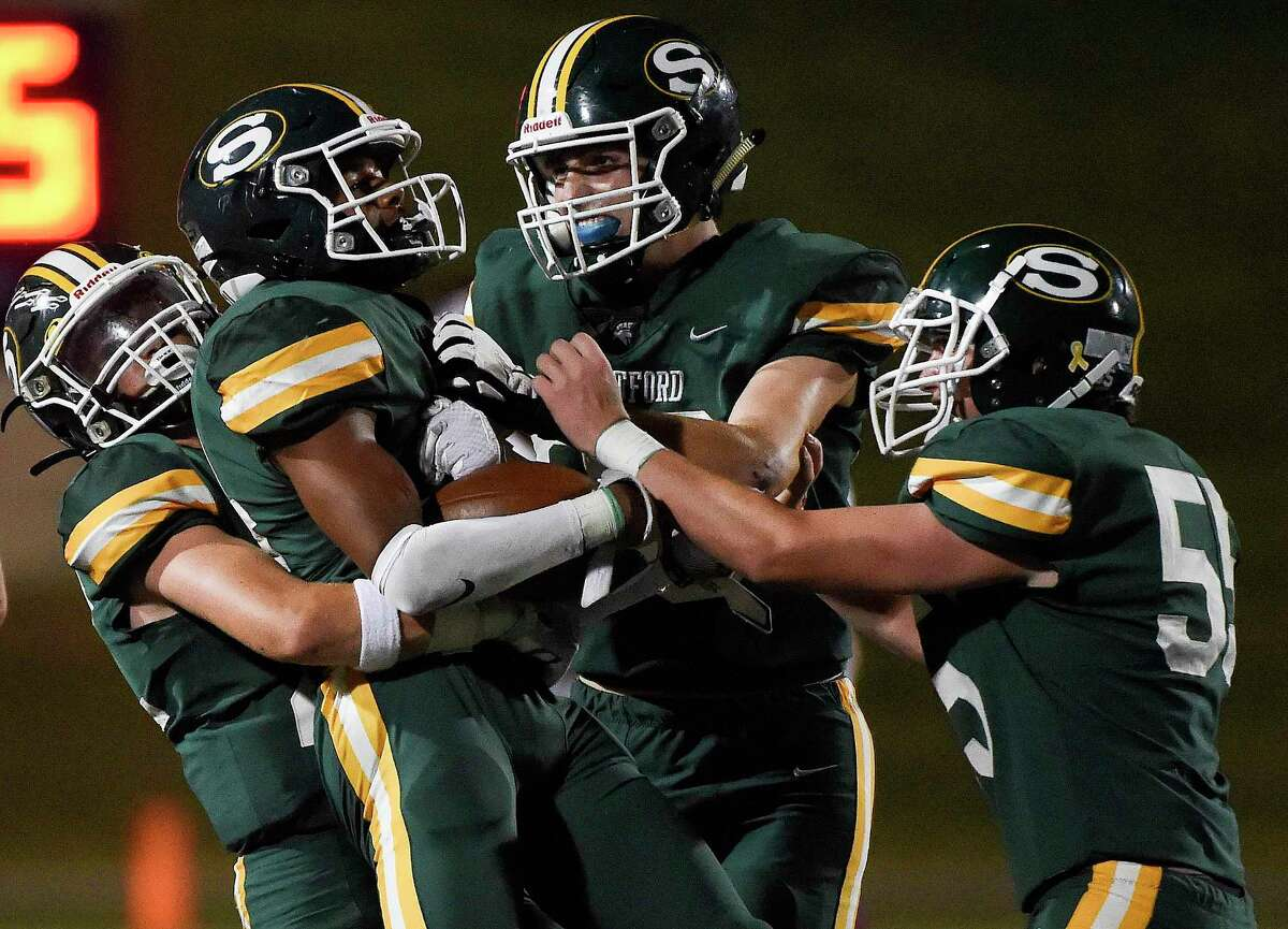Stratford defensive back Charles Mackey, second from left, celebrates his interception with Brecken Menuet, left, Dylan Schick, center, and Ryan Smith during the second half of a high school football game against Cy-Fair, Friday, Sept. 24, 2021, in Houston.