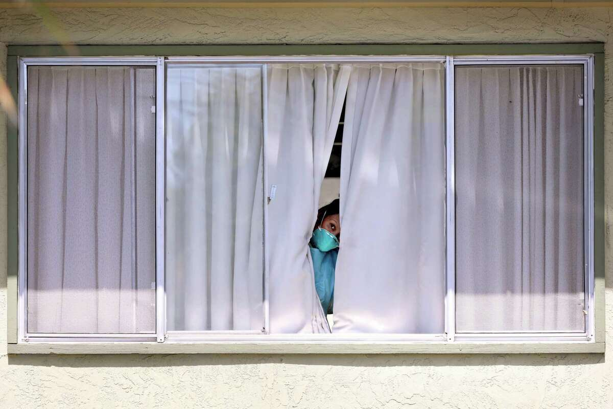 This file photograph shows an employee wearing protective gear peeks from a window after a patient was picked up by Falcon Critical Care Transport at Gateway Care and Rehabilitation on Wednesday, April 15, 2020, in Hayward, Calif.