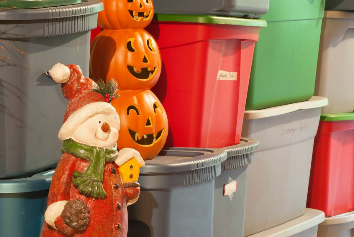 Plastic storage bins, filled with decorations for various holidays. xx