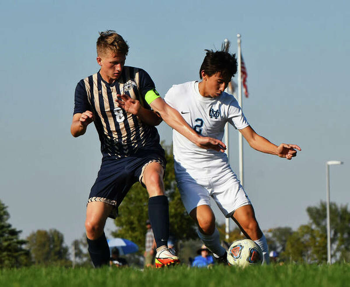 Father McGivney's Tanner Garner, left, battles for possession of the ball with Mater Dei's Cade Kramer early in the first half of a game Tuesday in Glen Carbon.
