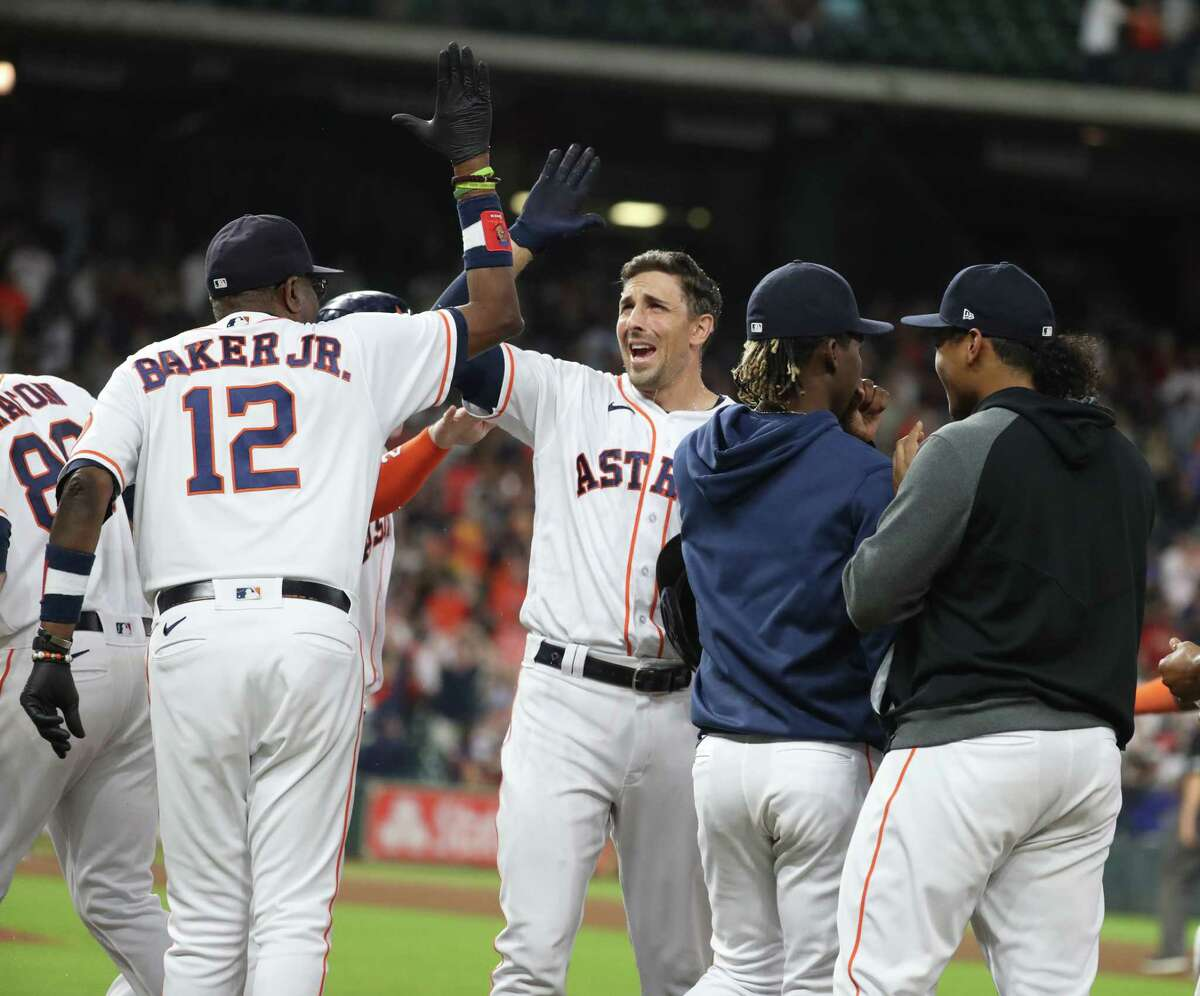 Houston Astros Jason Castro (18) celebrates with manager Dusty Baker Jr. (12) after drawing a walk from Tampa Bay Rays relief pitcher JT Chargois, scoring Carlos Correa for the winning run to end the ninth inning of an MLB baseball game at Minute Maid Park, Tuesday, September 28, 2021, in Houston.