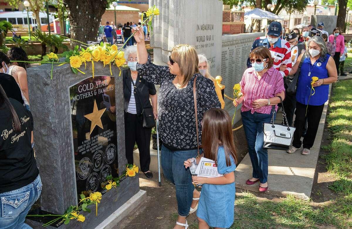 Familiares de Madres Estrella Dorada y de miembros del servicio caídos durante algún conflicto armado colocan flores en el recién erigido Monumento a las Madres Estrella Dorada, el sábado 25 de septiembre de 2021 en Jarvis Plaza.