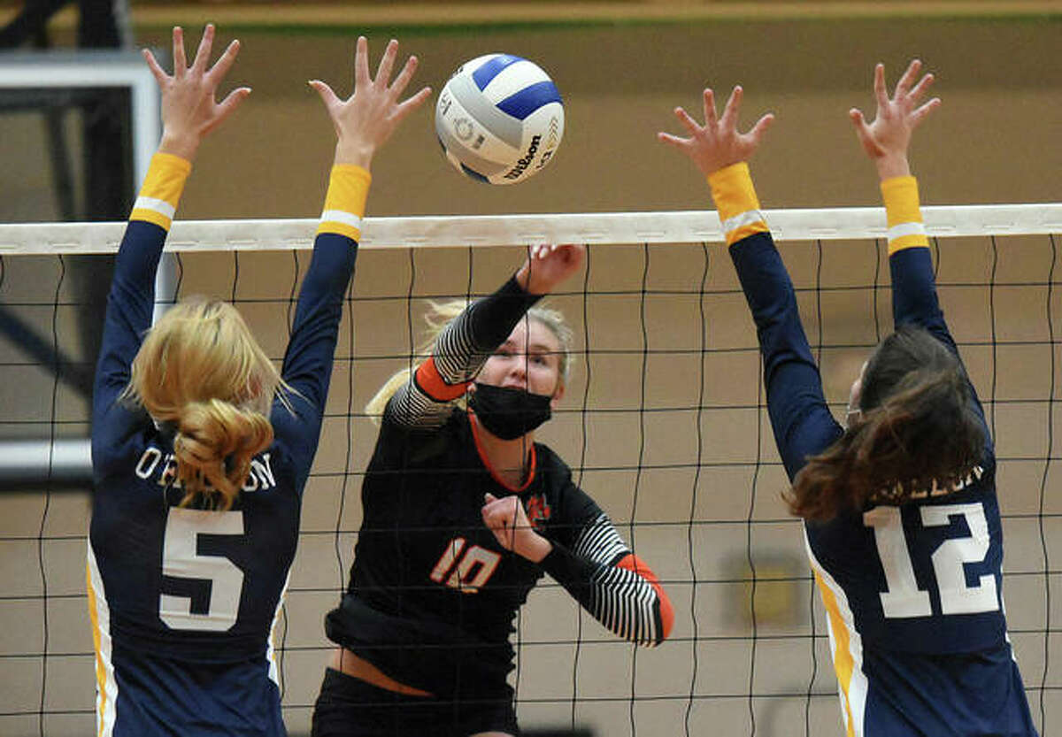 Edwardsville's Emma Garner splits a pair of O'Fallon defenders with a kill during the first game on Tuesday inside Lucco-Jackson Gymnasium in Edwardsville.