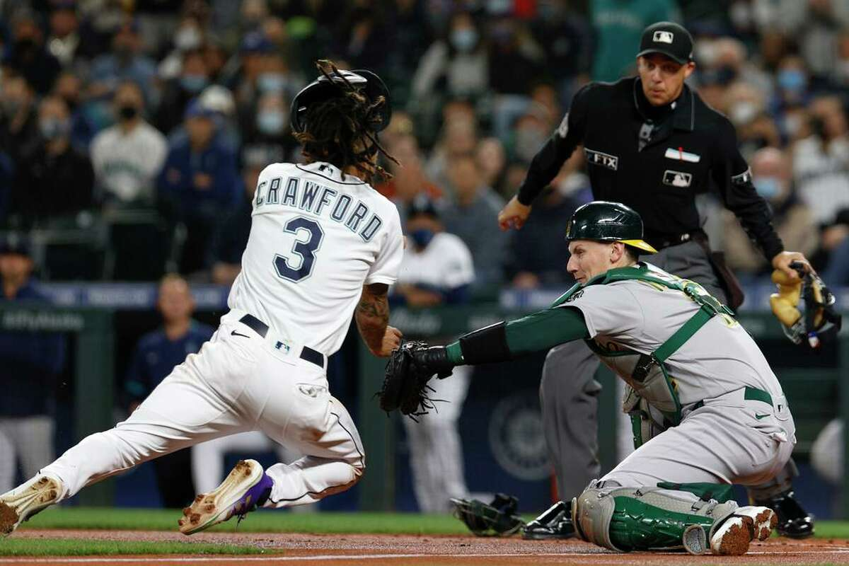 Oakland Athletics catcher Sean Murphy goes for the tag on Seattle Mariners' J.P. Crawford for the out at home plate in the first inning of a baseball game Tuesday, Sept. 28, 2021, in Seattle. (AP Photo/Jason Redmond)