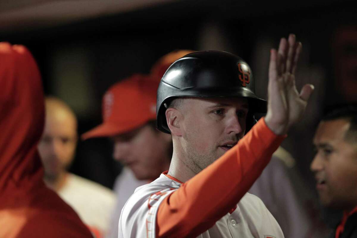 Buster Posey (28) high fives teammates in the dugout after he scored on a wild pitch in the sixth inning as the San Francisco Giants played the Arizona Diamondbacks at Oracle Park in San Francisco, Calif., on Tuesday, September 28, 2021.
