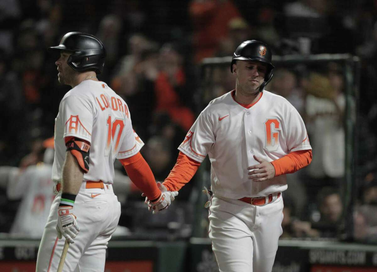 Buster Posey (28) high fives Evan Longoria (10) after he scored on a wild pitch in the sixth inning as the San Francisco Giants played the Arizona Diamondbacks at Oracle Park in San Francisco, Calif., on Tuesday, September 28, 2021.
