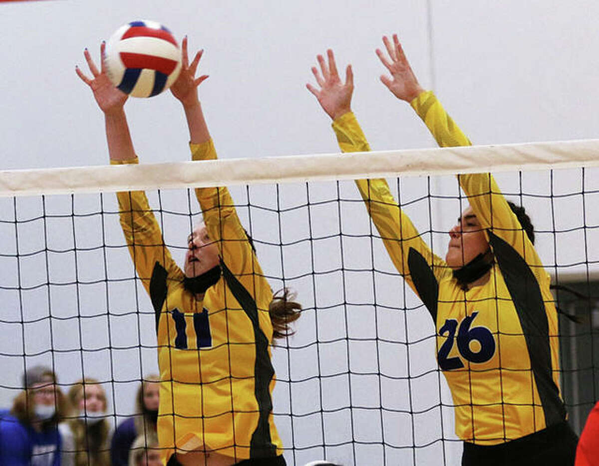 CM's Lauren Dunlap (left) gets to the ball from a double block with teammate Camryn Gehrs during a match earlier this season at the Roxana Tournament. On Tuesday, the Eagles picked up their 20th win by sweeping Jersey in Bethalto.