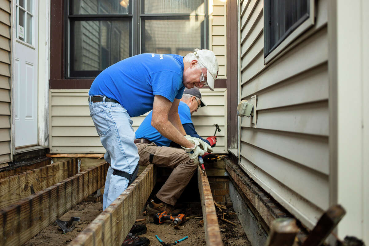 Volunteers John Kennan, left, and Bill Schramm, right, work to renovate the back porch at Safe and Sound Child Advocacy Center Wednesday, Sept. 29, 2021 in Midland. (Katy Kildee/kkildee@mdn.net)