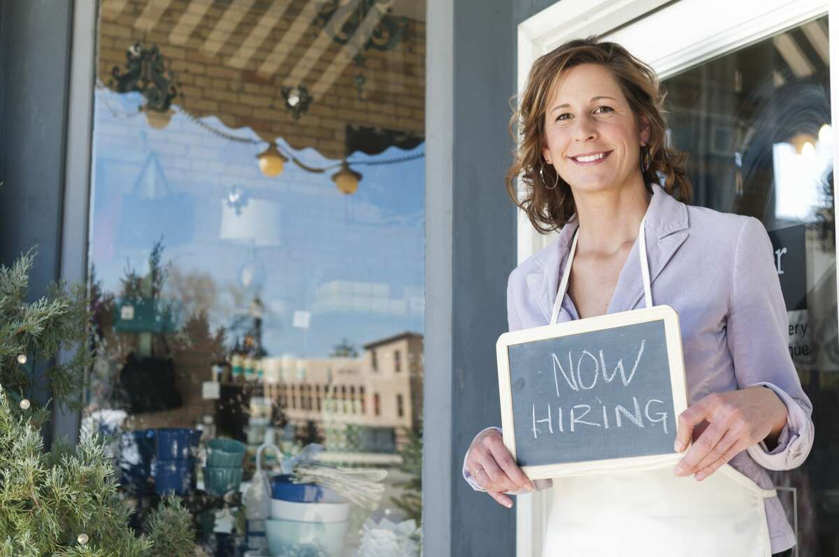 """Pictured is a business woman holding a """"Now Hiring"""" sign in front of store."""
