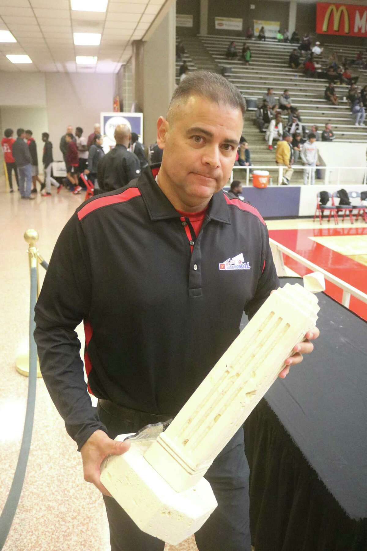 Pasadena ISD Athletic Director Rupert Jaso carries one of the McDonald's Texas Invitational limestone trophies before a championship game at Phillips Field House. Plenty of slots are open for volunteers at Phillips for the upcoming tournament Nov. 18-20.