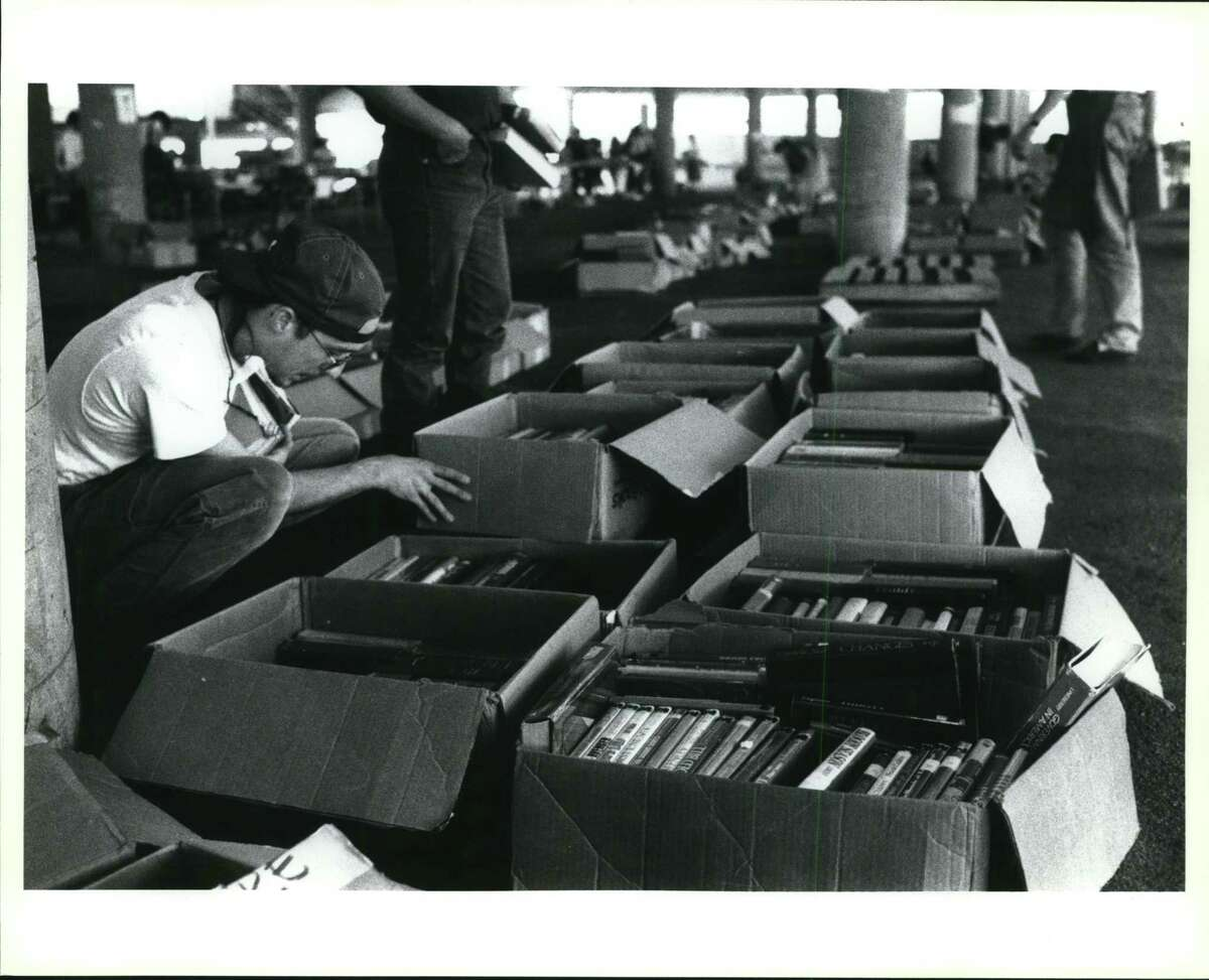 FILE PHOTO - Scott Power of San Antonio looks through boxes of books Sunday afternoon at the Friends of the San Antonio Public Library book sale at the old Sears parking garage.