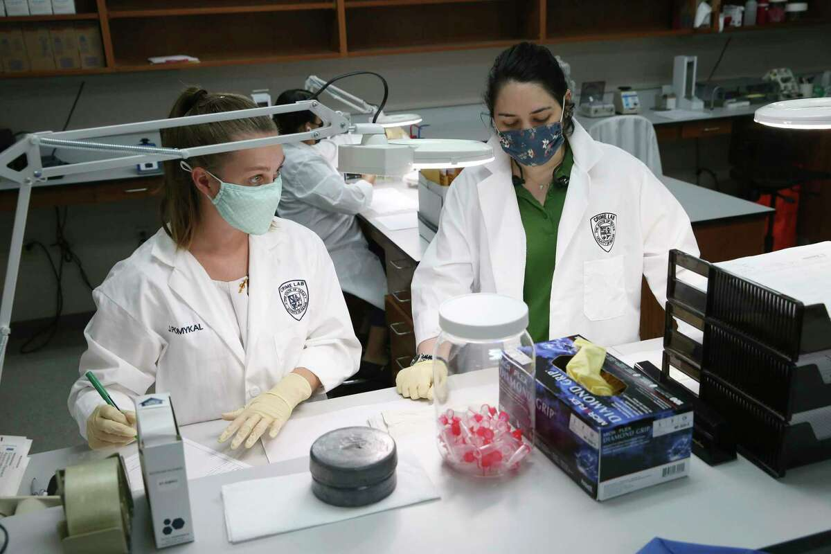 Forensic scientists Caitlin McCaughan, left, and Wesli Stubb, extract DNA from evidence at the Bexar County Crime Lab on Sept. 21, 2021.