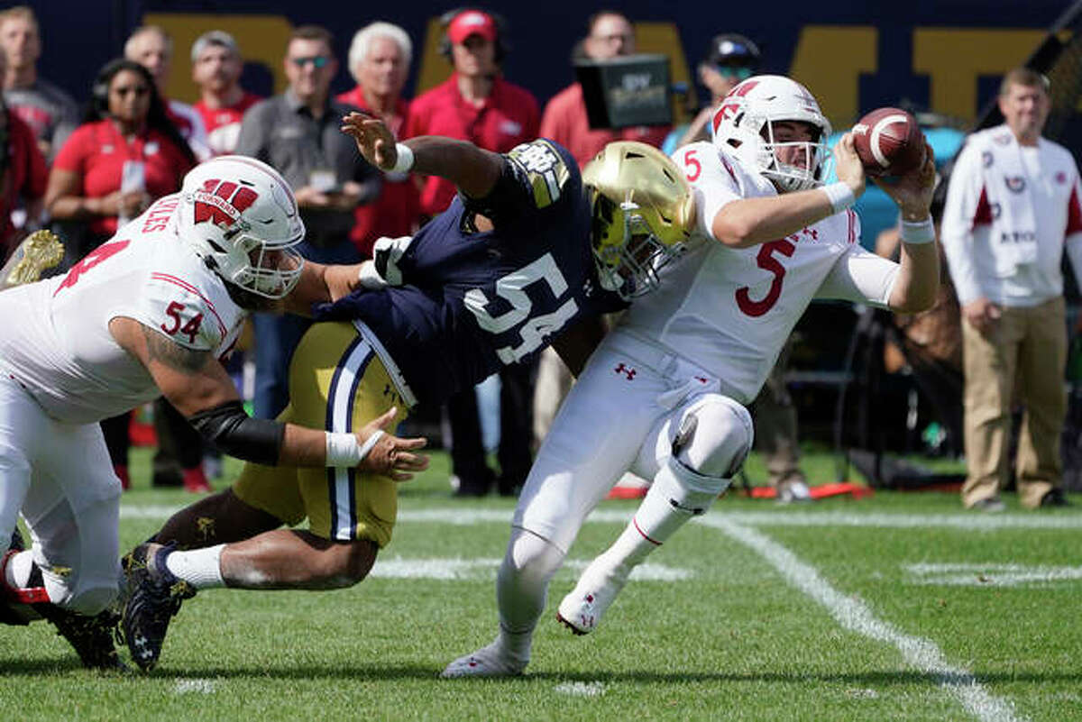 Wisconsin quarterback Graham Mertz (5) makes a two-handed pass to avoid the pressure from Notre Dame defensive lineman Jacob Lacey after Lacey got past lineman Kayden Lyles last Saturday in Chicago.