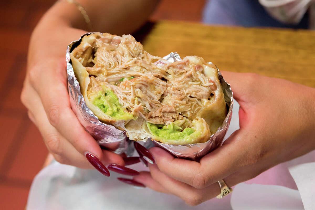 SFGATE burrito reviewer Cecilia Peña-Govea tries the super chicken burrito (dorado) at La Taqueria in San Francisco's Mission District.