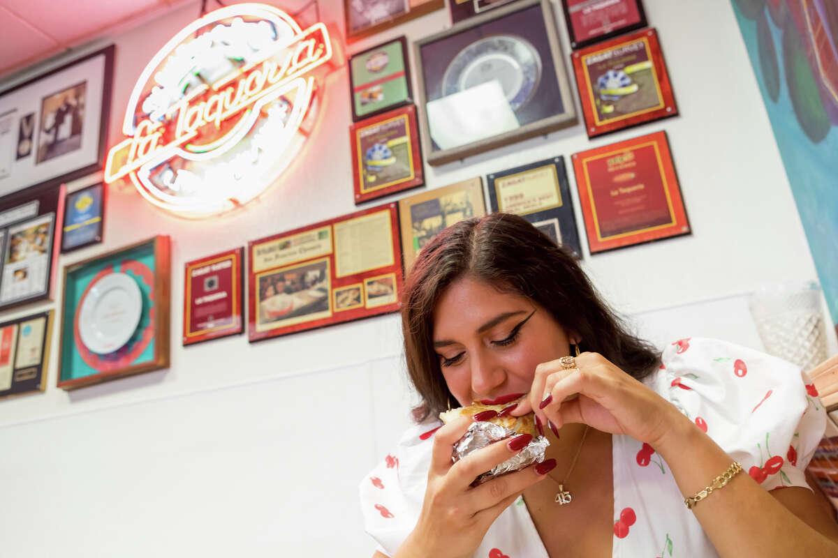 SFGATE burrito critic Cecilia Peña-Govea tries a burrito at La Taqueria in San Francisco's Mission District.