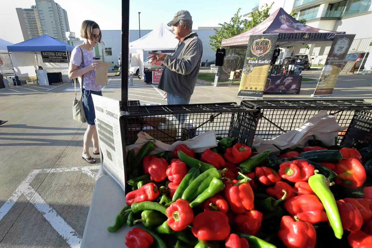 Customer Stephanie Marton, left, takes a flyer from Van Weldon, right, owner of Wood Duck Farms at their produce booth at the Urban Harvest Farmers Market Saturday, Sept. 25, 2021 in Houston, TX. Weldon's farm is located next to a proposed landfill and he is doing everything he can to fight it.